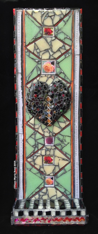 photo of glass mosaic. The mosaic features a black heart, studded with multi-colored beads. There is text lining the sides of the mosaic and it reads: we are brothers sister all. This is written in repetition. There is a diamond pattern in the background and the background is cream colored and minty green. The diamond pattern is laid out with very thin threads or rods of glass that are normally used in glass blowing. There are five photographs of roses placed throughout the diamonds. There is a floor to this mosaic, kind of like a small altar and the glass is laid in a black/white pattern on thefloor. Thank you for taking the time to experience my work.