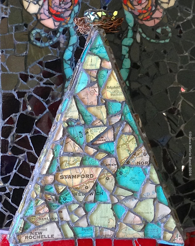photo of a glass mosaic on wood, triangle shaped, clear glass over a map