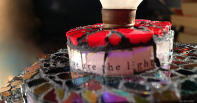 Picture of glass mosaic on wood detail with text that says: we are the light of the world under glass and iridescent glass