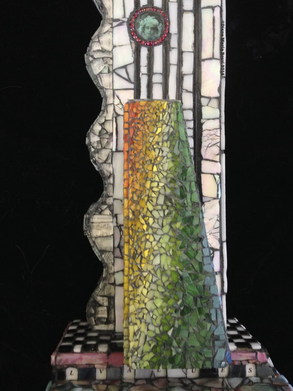 Picture of glass mosaic on wood detail rainbow ( yellow to green) with photo of Aunt Jean surrounded by Lisa's beads with checked floor and lines of the staff