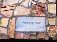 Picture of glass mosaic on wood gold glass with text of business card under glass that says: Vulcan Scrap Metal Co. Non-Ferrous Metals and Scrap Junk Cars  105 Worth Street Stamford, Conn Fireside 8-4339 Carmine Longo / Art Rossi