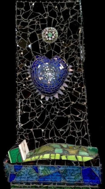 photo of glass mosaic on wood/ blue heart with lavender, white spokes in black background with  bed on bottom and brooch in blackbackground. black background has mirror as stars