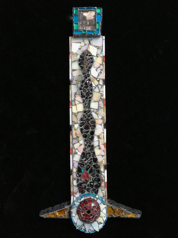 glass mosaic totem on wood with photograph from Portugal or Spain on the top --- an image of a goddess. The piece has a black snakelike form going down the length of the piece and on the bottom, there is a red round shape, kind of like an eye or an orb surrounded by white triangles in a white background. The circle is ringed with turquoise glass and there are amber colored glass triangles like flippers on the bottom.