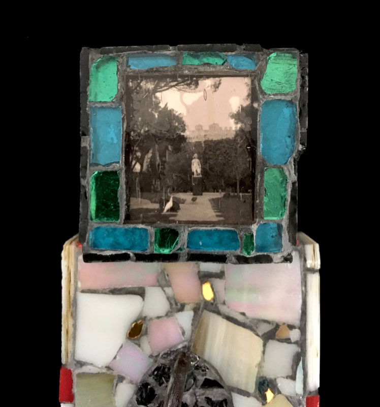 detail of Eve's Place Redux - the top tv head part -- a cube with a photo of a park in either Spain or Portugal of a woman's statue. The photo is in black and white with a pink cast and is surrounded by green and aqua colored glass